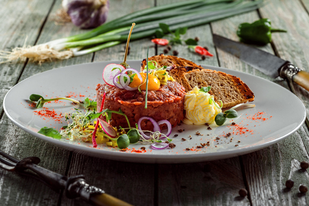 Plate with delicious tartare, toasted bread and salad on a wooden table. Healthy gourmet French food made of raw meat.