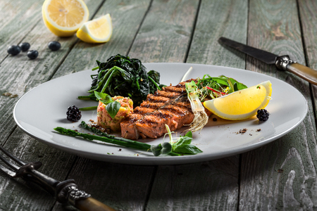 Grilled salmon fish steak with vegetable salad on a plate. Gourmet seafood meal made of fish and vegetables. Healthy food on a table.