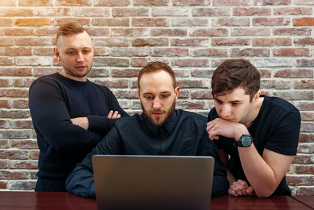 Group of young and creative IT people working in an office. Three programmers looking for successful decision.