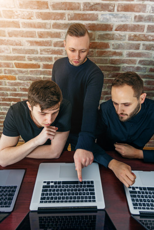 Group of successful young men working together in the office. Three creative programmers looking for solution. Stock Photo