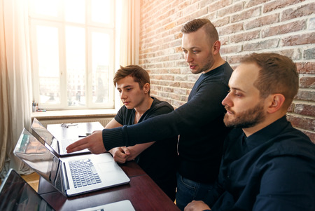 Team of three young men working in the office. Group of coders looking for creative decision directing by team leader. Stock Photo