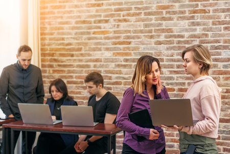 Two female employees analyzing a problem to find a decision. Group of successful young men and women working together in the office Stock Photo