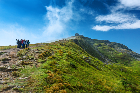 Group of tourists taking selfie photo on a summit of a mountain. Landscape of Carpathian mountains with people. Stock Photo