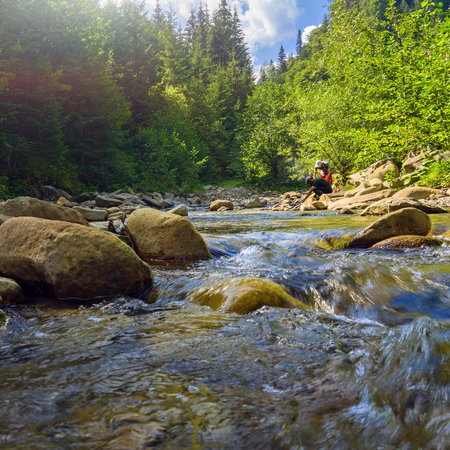Two tourists are fetching water from mountain river in summer Carpathians. Landscape of forest stream in mountains with people.
