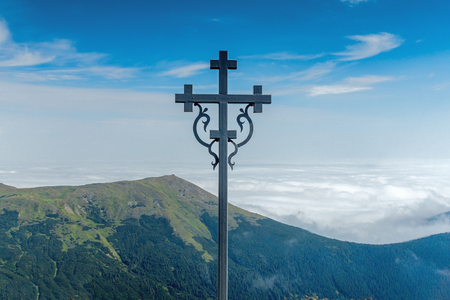 Landscape of mountain chain in a clouds and cross on foreground. Carpathian Mountains in a summer sunny day.
