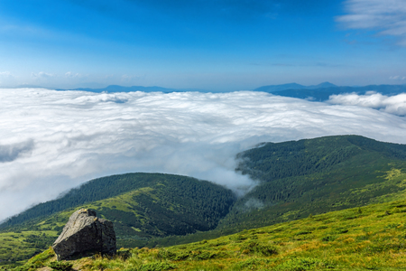 Landscape of mountain in a clouds and rock on foreground. Carpathian Mountains in a summer sunny day.