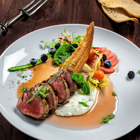 Medium rare meat steak medallions with sauce and salad on a plate. Delicious healthy food made of meat with vegetables and wine for lunch.