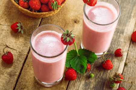 Delicious fruit milkshake made of fresh ripe strawberry and milk. Diet drink for healthy breakfast. Top view. Stock Photo