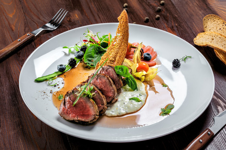 Gourmet medium rare meat steak with sauce and fresh salad. Healthy meal made of meat fillet and fresh vegetables on a rustic table.