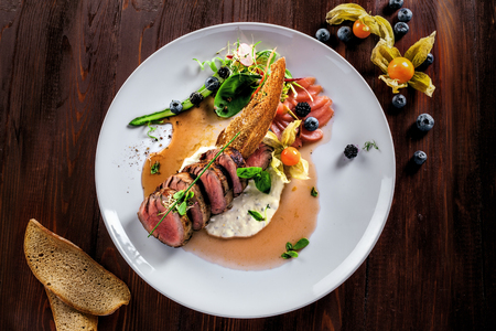 Delicious medium rare meat steak with sauce and salad on a plate. Healthy food made of meat fillet and fresh herbs on a wooden table. Top view. Stock Photo