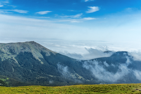 Landscape of mountain chain in a clouds. Carpathian Mountains in a summer sunny day.