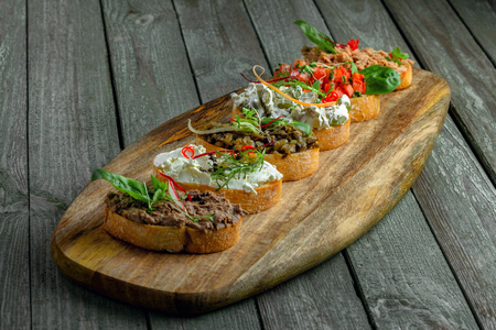 Bruschetta set made of tomato, meat pate, olives, cream cheese and tuna salad on a rustic wooden board. Delicious Italian antipasti. Zdjęcie Seryjne