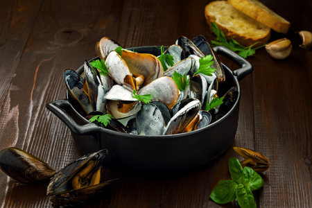 Delicious Steamed Mussels With Wine And Cream on a table. French meal Moules marinière in a bowl. 免版税图像