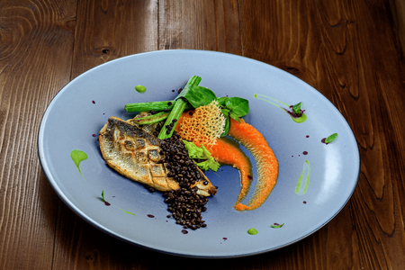 Plate with delicious grilled seabass fish fillet steak and vegetables on a brown wooden table. Healthy gourmet food. Stock Photo
