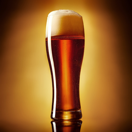 Draft brown ale beer in a  glass on a golden gradient background. Imagens