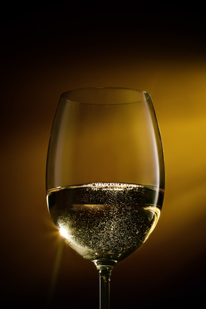 Sparkling white wine in a glass on a gradient black to yellow background. Studio shot.