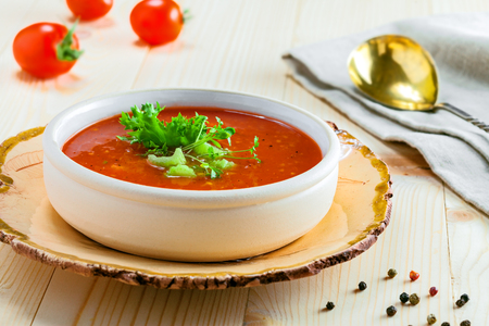 Delicious gazpacho and ingredients on a table. Vegetarian vegetable cold soup.