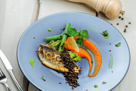 Gourmet grilled seabass fish fillet steak and vegetable salad. Delicious healthy meal made of seafood and vegetables on a rustic table. Top view shot. Stock Photo