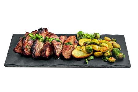 Comida gourmet a base de bistec para perchas, coles de Bruselas, patatas y cebolla sobre una tabla de piedra. Filete de carne rara medio sabroso con verduras aislado sobre un fondo blanco. Foto de archivo