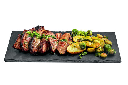 Gourmet meal made of hanger steak, brussels sprouts, potatoes and onion on a stone board. Tasty medium rare meat steak with vegetables isolated on a white background. Imagens