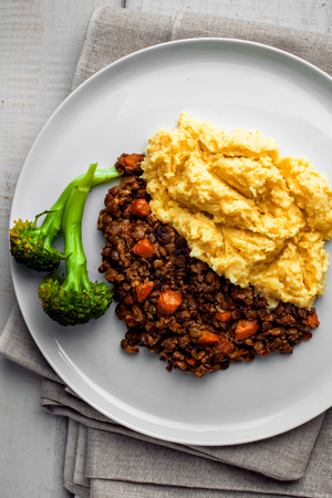 Shepherds pie on a plate. Delicious meat pie made of smashed potatoes, minced meat, lentil and vegetables. Top view, above shot. Stock Photo