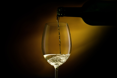 Wine glass is filling with white wine from a bottle.Close-up studio shot on a dark background.