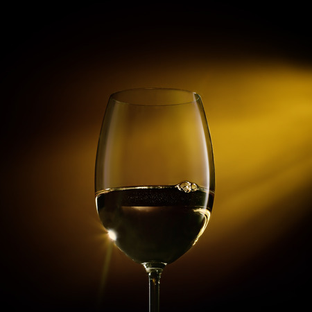 Glass of white wine on black to yellow background. Concept studio close-up shot.