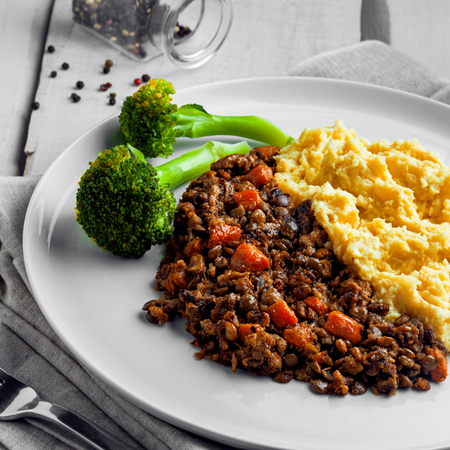 Plate of shepherd's pie on a white wooden table. Meal made of smashed potatoes, minced meat, lentil and vegetables.