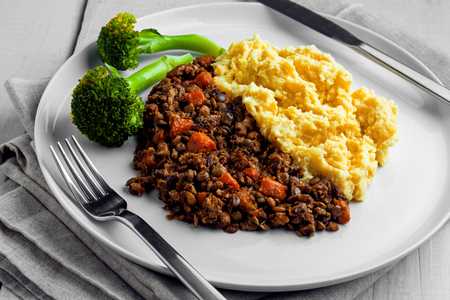 Shepherd's pie on a plate. Delicious meat pie made of smashed potatoes, minced meat, lentil and vegetables.