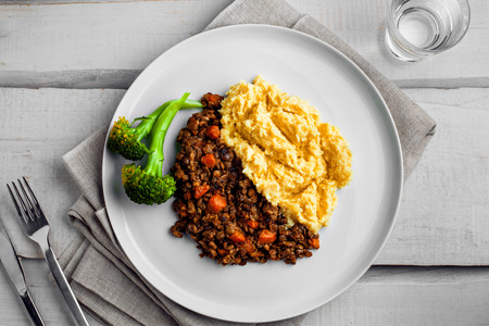 Plate of shepherd's pie on a white wooden table. Meal made of smashed potatoes, minced meat, lentil and vegetables. Top view, above shot. Stock Photo