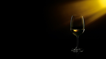 White wine in a glass on a gradient black to yellow background. Studio shot.