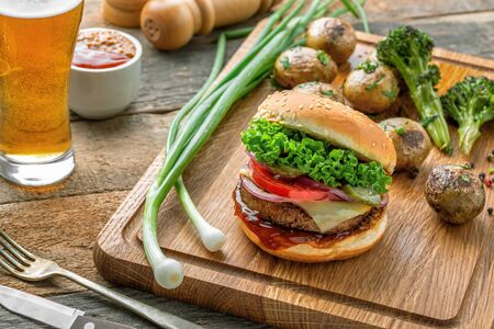 Hamburger with grilled vegetables and scallion served on a wooden board and a glass of beer on a rustic tale.