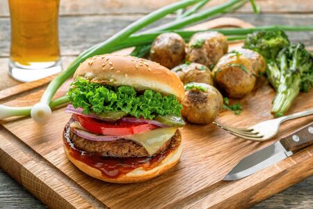 Delicious cheeseburger with baked potatoes, broccoli and scallion on a cutting board served with a glass of lager beer.
