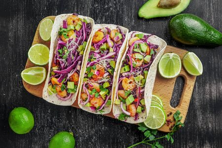 Tacos made of prawns, avocado, red onion, cabbage and lime on a table. Delicious Mexican cuisine meal. Top view shot, directly above.