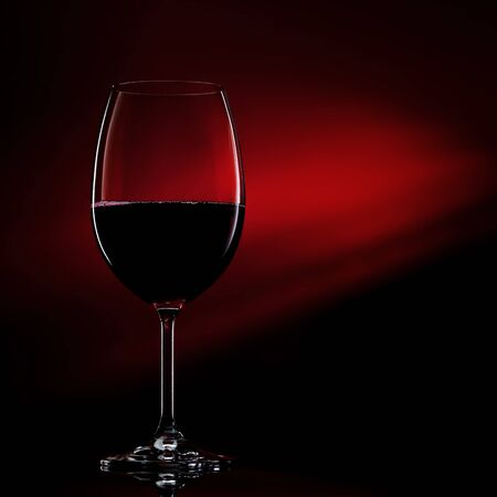 Glass of red wine on black to red gradient background. Concept studio shot. Фото со стока