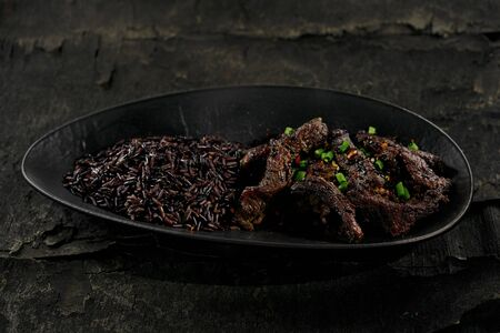 Sticky Asian beef stir fry in salty sweet sauce with black rice in a black clay plate. Foto de archivo