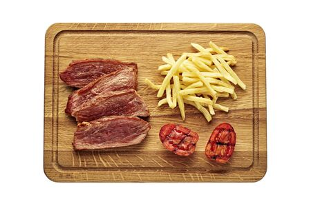 Medium rare sirloin steak with chips and grilled tomatoes isolated on white background. Classic European lunch studio flat lay shot. Top view, directly above.