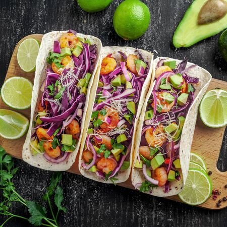 Delicious tacos with shrimps, avocado, onion and lime on a wooden board. Classic Tex-Mex cuisine meal. Top view shot, directly above.