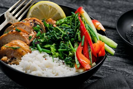 eriyaki chicken fillet, fresh cucumber, red bell pepper, stew cabbage and basmati rice Traditional Asian Buddha bowl meal.