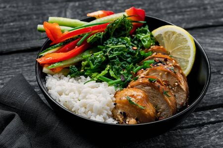Delicious Buddha bowl with teriyaki chicken, fresh vegetables and basmati rice on a black table with dark tablemat.