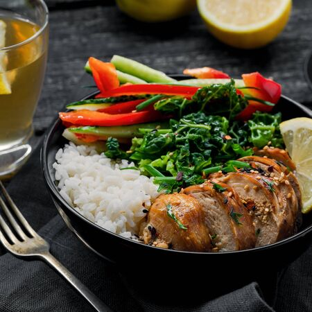Buddha bowl meal with teriyaki chicken fillet, fresh vegetable salad, stew cabbage and basmati rice on a rustic table. Delicious dish in a black bowl with homemade lemonade. Stock Photo