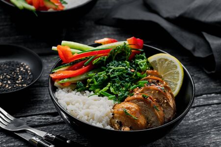 Two lunch bowls with teriyaki chicken, cucumber, red bell pepper, green onion, stew spinach and basmati rice on a rustic black table. Stock Photo