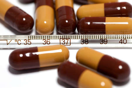 Some medicine capsules and one thermometer isolated on white photo