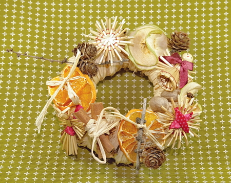 Christmas straw wreath decoration - photo captures and presents various details of Christmas straw wreath, such as dried orange and apple, straw figurines    photo