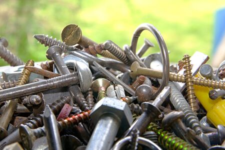 Photo shows mixture of various screws with green background. photo