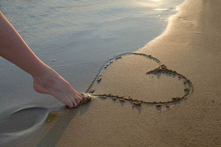 Photo shows a detail of the  heart written in the sand. photo