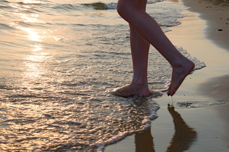 Legs with a sunset above the beach and sea. photo