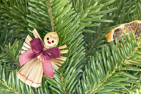 Photo shows a closeup of Christmas decoration from tree and figurine. photo