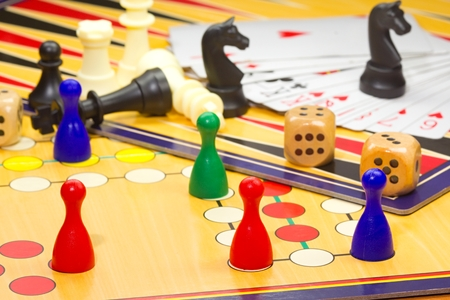 Photo shows a closeup of a various board games including chess and cards. Stockfoto
