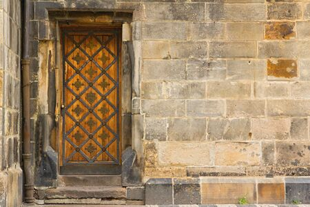 Photo shows a closeup of the old wooden doors in the Old Town of Prague. photo